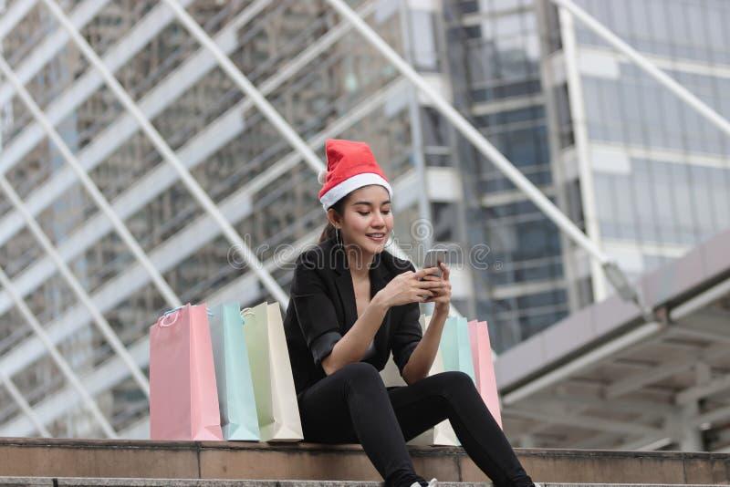 有圣诞老人帽子的可爱的年轻亚裔妇女和使用流动巧妙的电话的五颜六色的购物袋在网上购物的圣诞节g 免版税库存图片