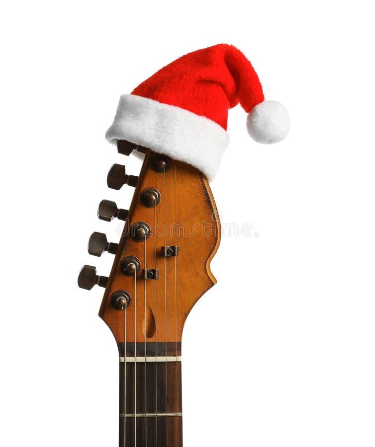 有圣诞老人帽子的吉他在白色背景 库存图片