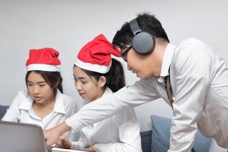 有圣诞老人帽子的愉快的青年人在家在网上购物与膝上型计算机的小组在客厅 圣诞快乐和新年好 免版税库存照片