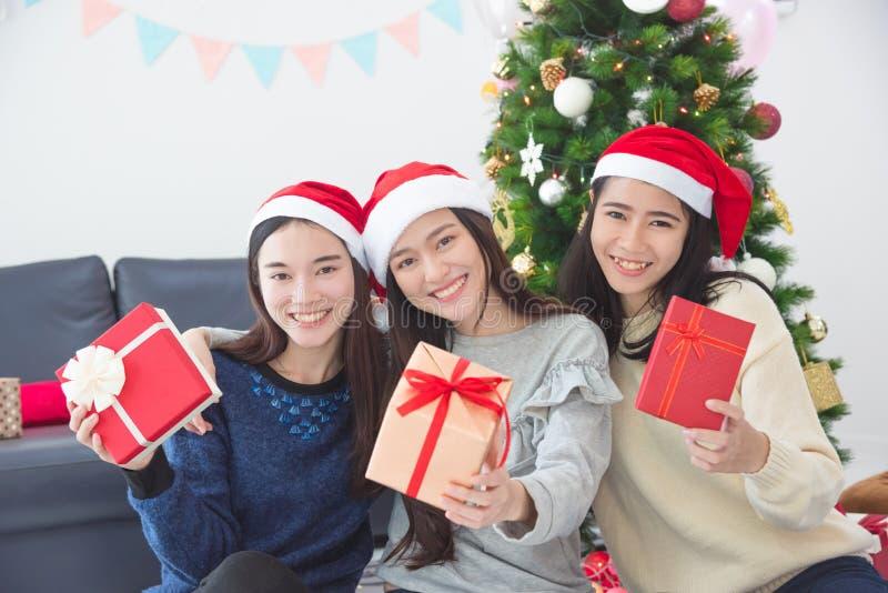 有圣诞老人帽子藏品礼物盒和微笑的三个女孩 免版税库存照片