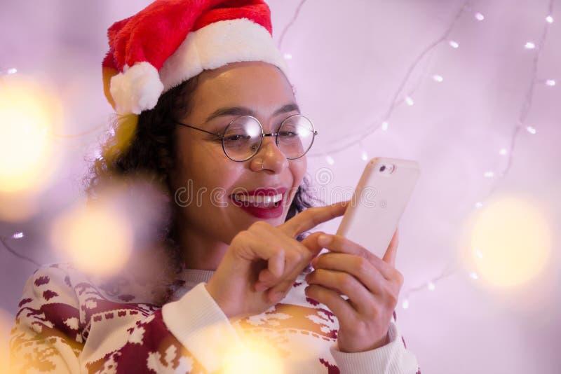 有圣诞老人项目帽子和圣诞节毛线衣使用的美女 免版税图库摄影