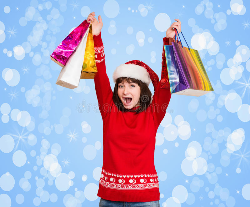 有圣诞节圣诞老人帽子的女孩在她的头,拿着shopp 免版税库存照片