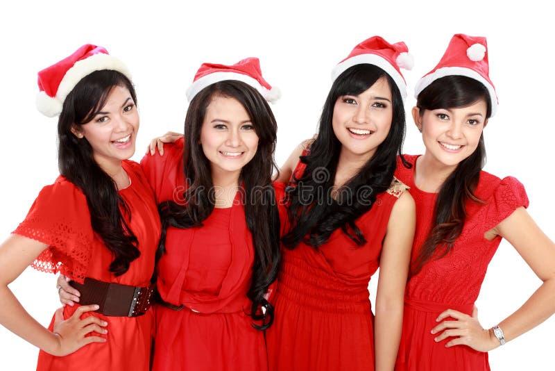 有圣诞节圣诞老人帽子的愉快的年轻人四亚洲人妇女 免版税库存图片