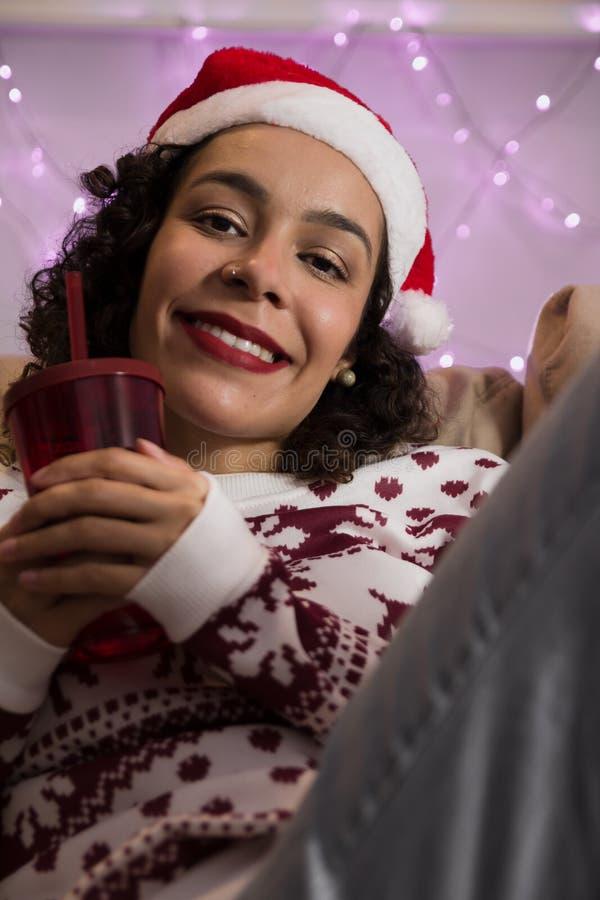 有圣诞节帽子和季节性毛线衣的a非裔美国人的妇女 免版税库存照片