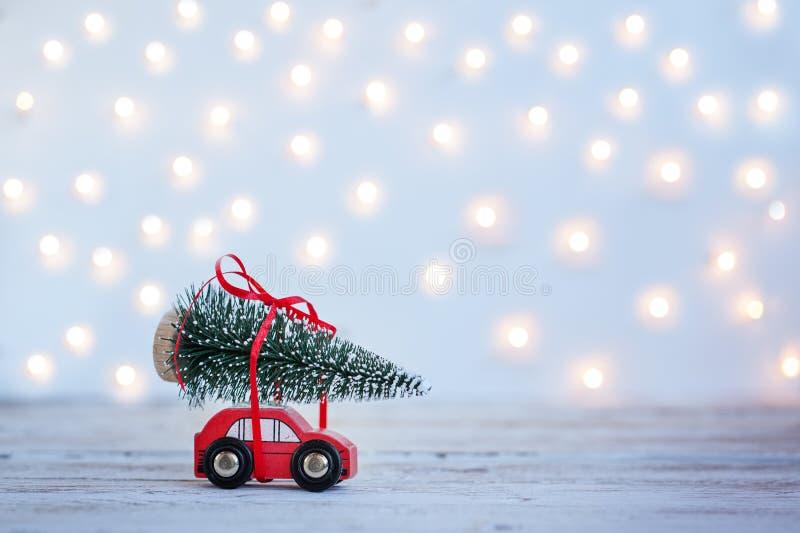 有圣诞节杉树的微型红色汽车在木背景 节假日概念 库存照片