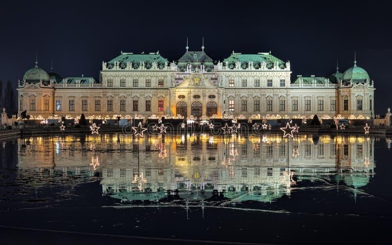有圣诞节村庄的贝尔维德雷宫在维也纳在夜,奥地利 免版税库存照片