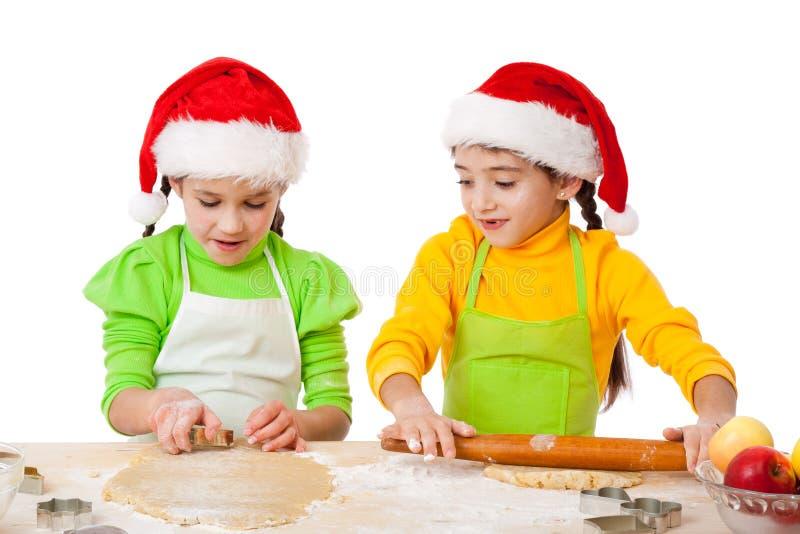 有圣诞节烹调的二个微笑的女孩 免版税库存照片