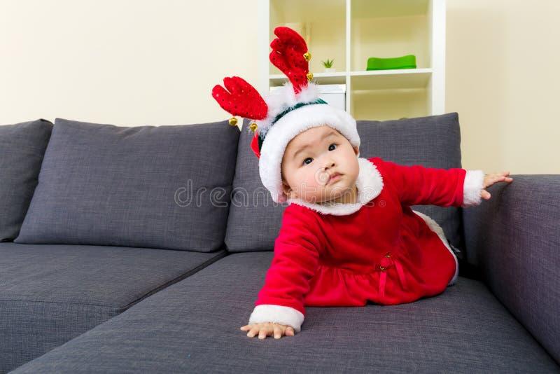 有圣诞节的女婴穿戴和爬行在沙发的 免版税库存图片