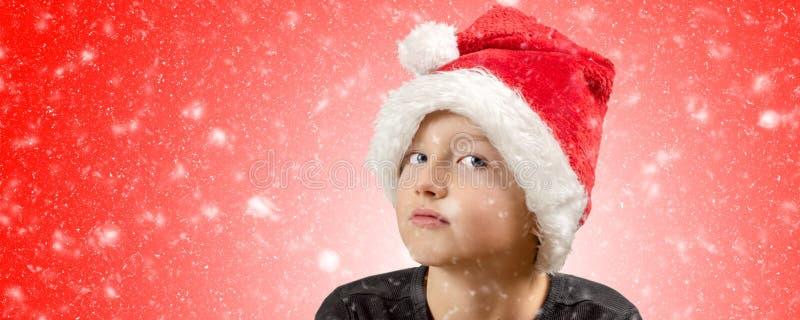有圣诞节盖帽和冬天大气的年轻乏味男孩 图库摄影