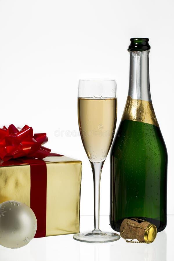 有圣诞节礼品的香槟槽和瓶 免版税库存照片