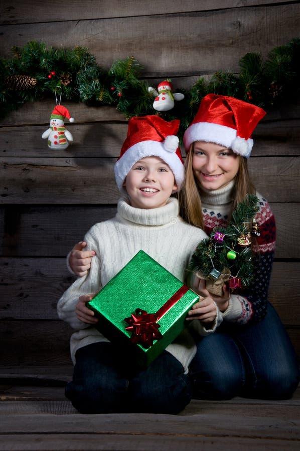 有圣诞节礼物和新年树的惊奇的愉快的孩子。做礼物。 图库摄影