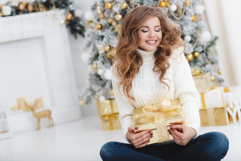 有圣诞节礼物的女孩在美丽的穿戴的圣诞树附近 图库摄影