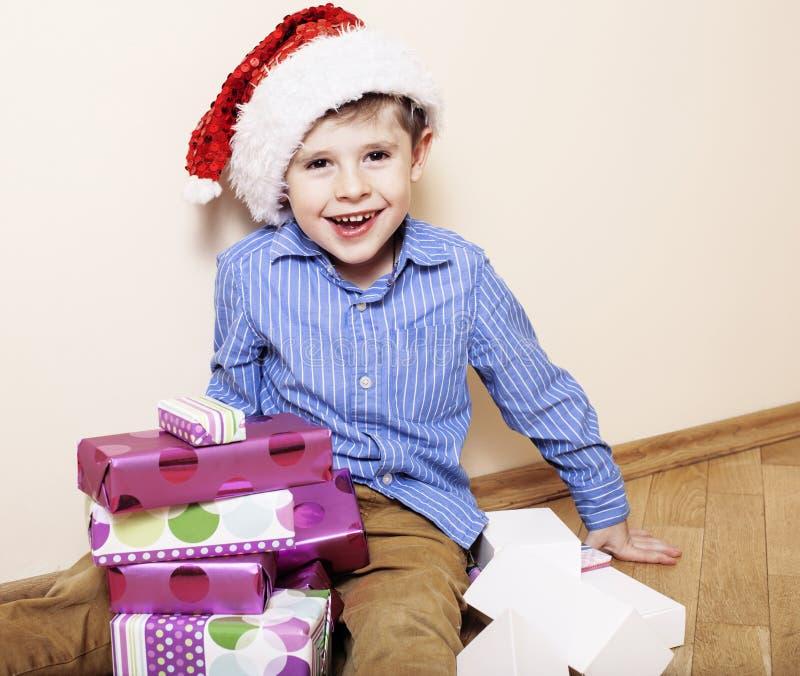 Download 有圣诞节礼物的小逗人喜爱的男孩在家 关闭在箱子的情感面孔在圣诞老人红色帽子 库存图片 - 图片 包括有 帽子, 表面: 72369833