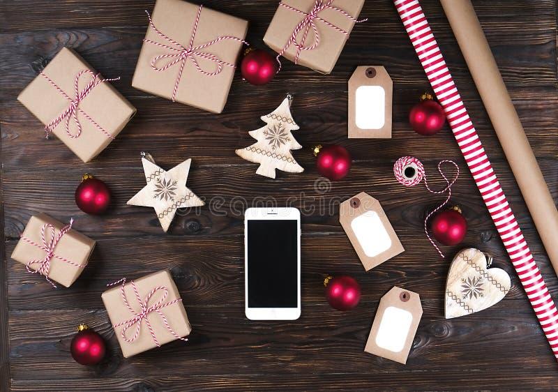 有圣诞节礼物的巧妙的电话在木背景顶视图 网上假日购物概念 平的位置,文本空间 互联网 免版税图库摄影