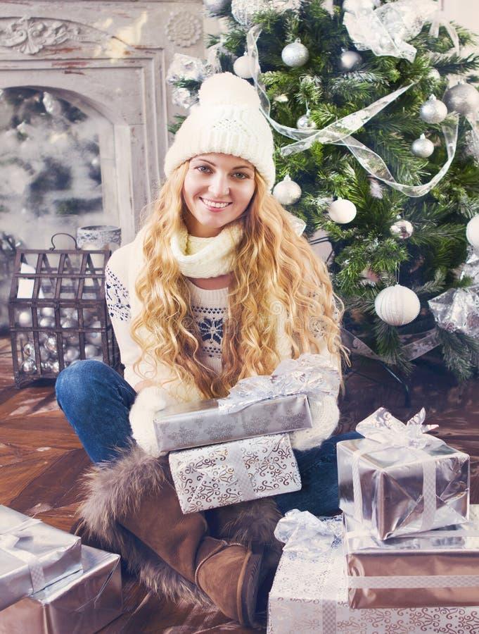 有圣诞节礼物的愉快的少妇在她的手上 库存照片