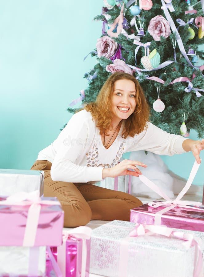 有圣诞节礼物的愉快的少妇在她的手上 免版税库存照片