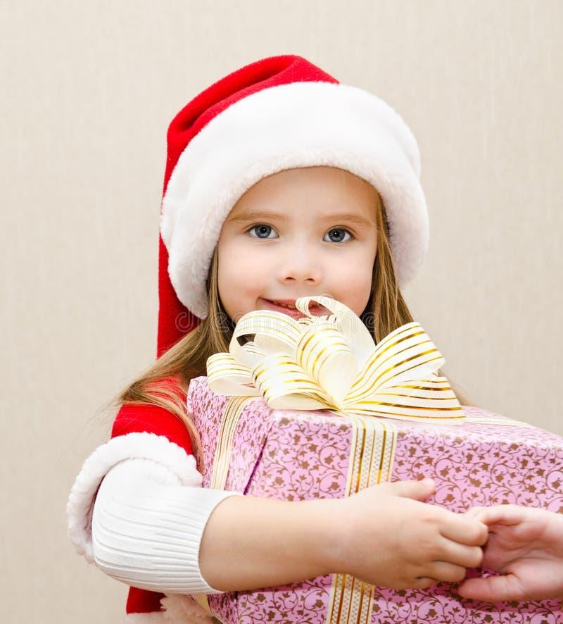 有圣诞节礼物的愉快的微笑的小女孩 图库摄影