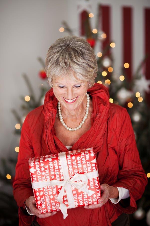 有圣诞节礼物的愉快的美丽的前辈 库存照片