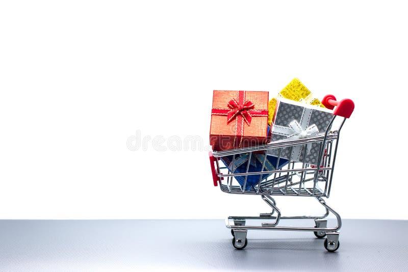 有圣诞节礼物的购物台车在白色背景,拷贝s 库存照片