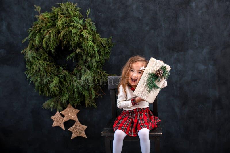 有圣诞节礼物盒的愉快的微笑的女孩 免版税图库摄影