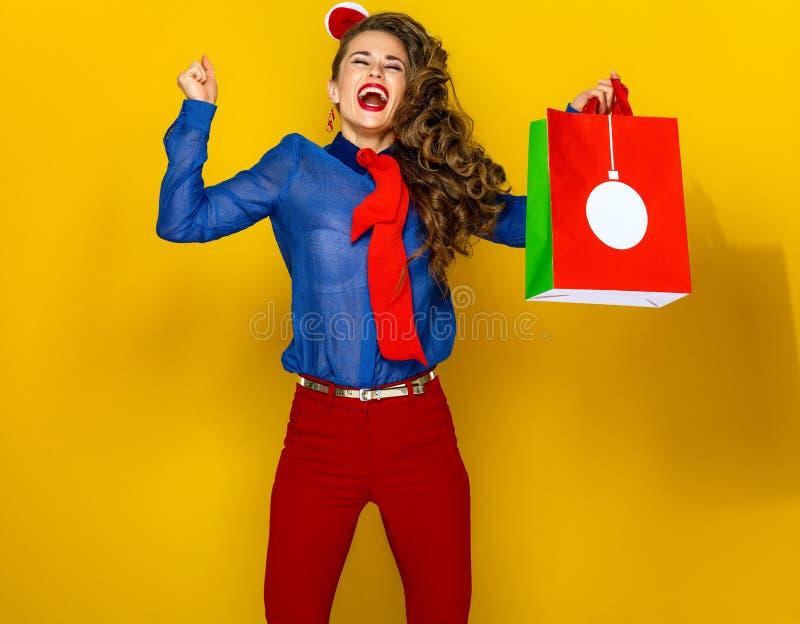有圣诞节购物袋欣喜和跳跃的微笑的妇女 免版税库存照片
