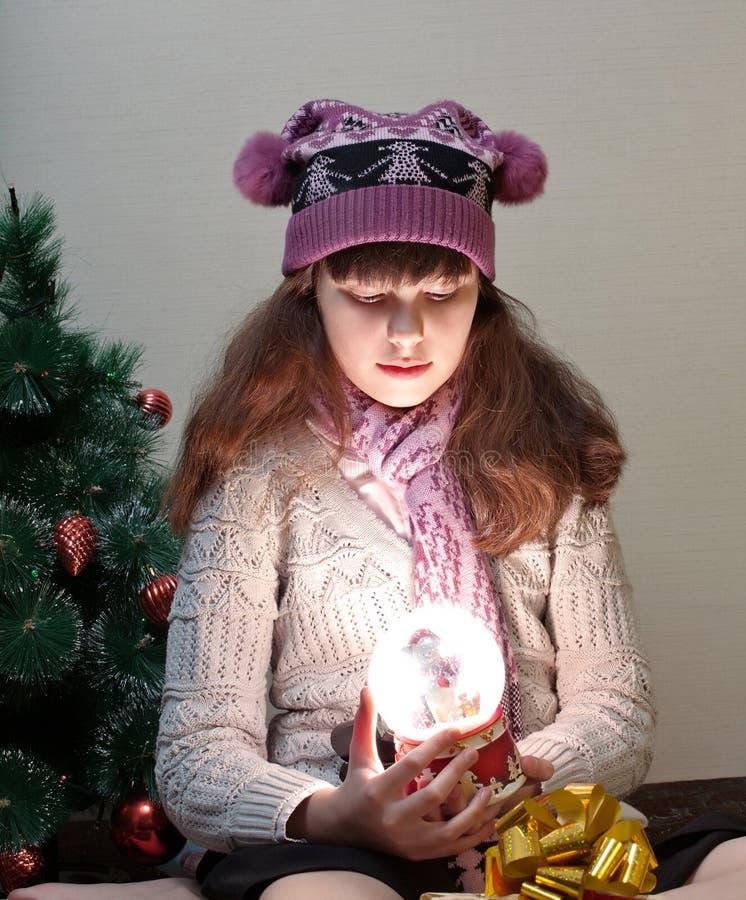 有圣诞节雪地球的女孩 库存图片
