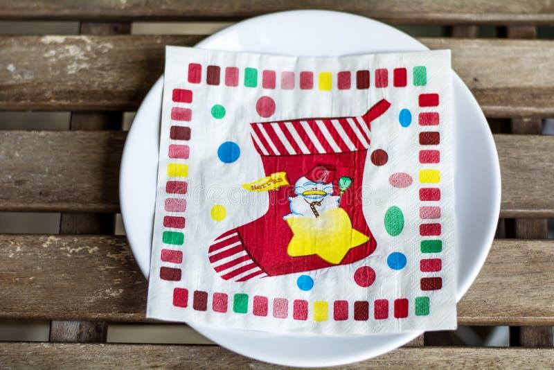 有圣诞节餐巾的白色板材 圣诞节桌与圣诞节装饰的餐位餐具 免版税库存图片