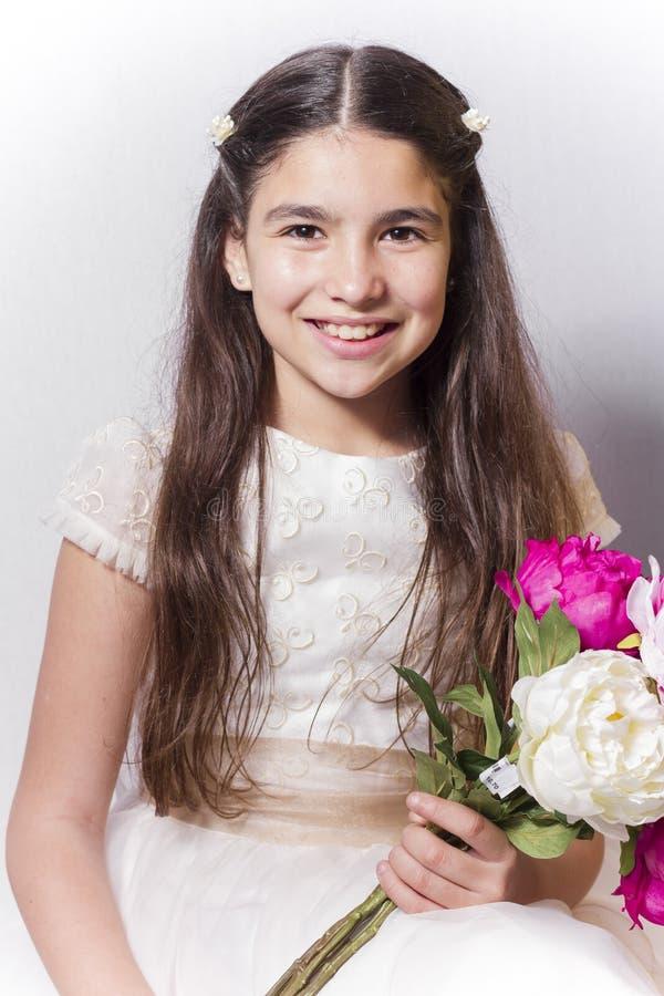 有圣餐的微笑的女孩穿戴拿着牡丹花束  免版税库存图片