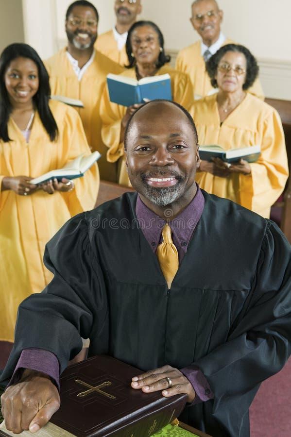 有圣经的传教者,当站立在背景中的唱诗班在教会时 免版税库存图片