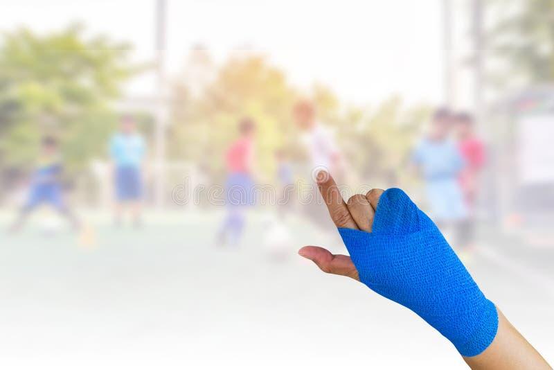 有在一个在手边隔绝的蓝色有弹性绷带的受伤的妇女 图库摄影