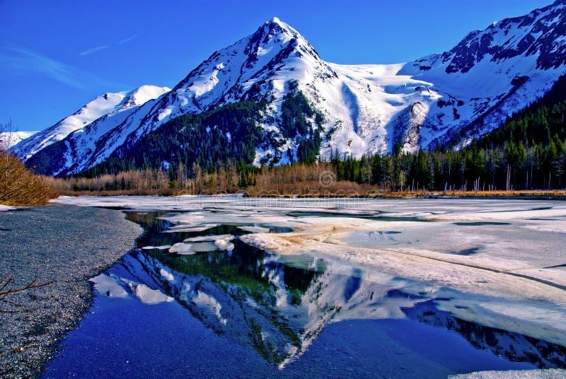 有在一个湖的部分地冻水域反映的山脉的一个部分地冻湖在伟大的阿拉斯加的原野。 库存照片