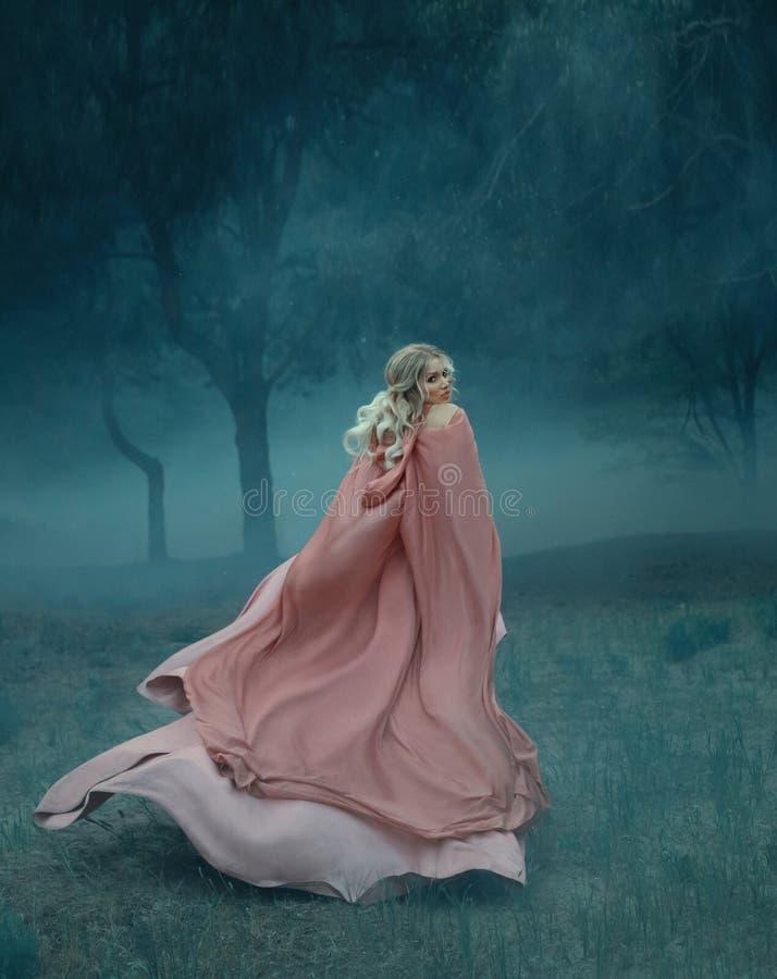 有在一个黑暗和密集的神奇森林里白色薄雾充分运行的金发的童话巫婆,穿戴在长 库存照片