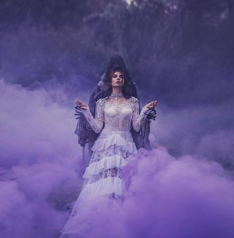 有在一件白色葡萄酒礼服和一条银色项链穿戴的红色嘴唇的一位黑暗的女王/王后在一个邪魔身分的胳膊在a 免版税库存图片