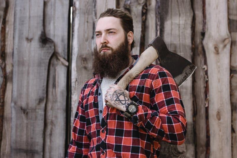 有在一件被检查的衬衣穿戴的胡子的残酷坚强男人站立与一个轴在手上以a为背景 库存图片