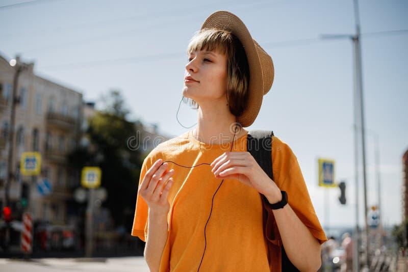 有在一件黄色T恤杉和草帽穿戴的耳机的微笑的少女走与沿城市街道的一个背包 库存图片