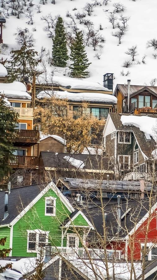 有在与厚实的雪的山修筑的五颜六色的外墙的垂直的框架家在冬天 免版税库存照片