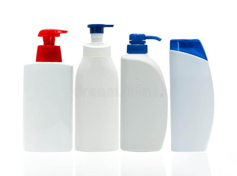 有在与空白的标签的白色背景隔绝的红色和蓝色泵浦分配器的化妆白色塑料瓶 套四皮肤 免版税库存照片
