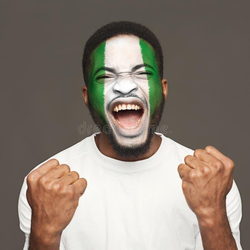 有在他的面孔绘的尼日利亚旗子的年轻人 免版税库存图片