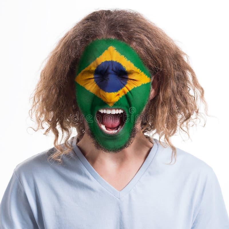 有在他的面孔绘的巴西旗子的年轻人 库存照片