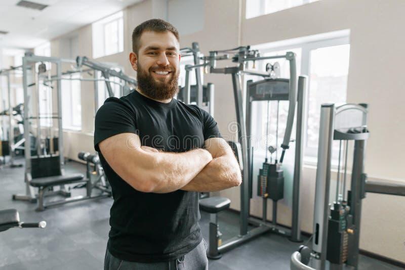 有在健身健身房横渡的胳膊的微笑的正面确信的男性个人辅导员 免版税库存照片