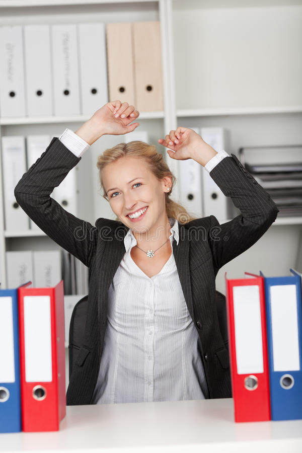 有在办公室举的胳膊的成功的女实业家 免版税库存图片