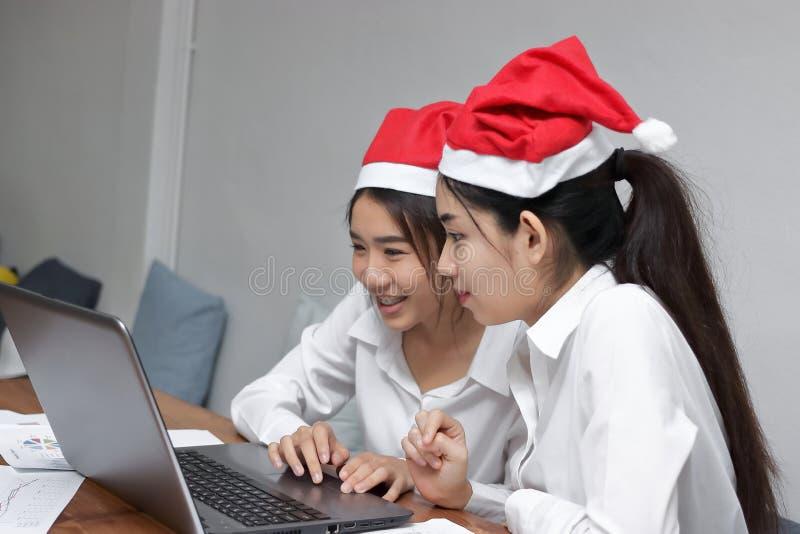 有在办公室工作场所的圣诞老人帽子的两个快乐的年轻亚裔女商人  免版税库存照片