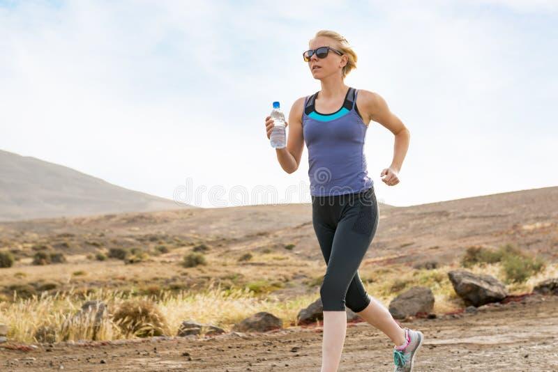 有在土路跑的水瓶健身的妇女 免版税图库摄影