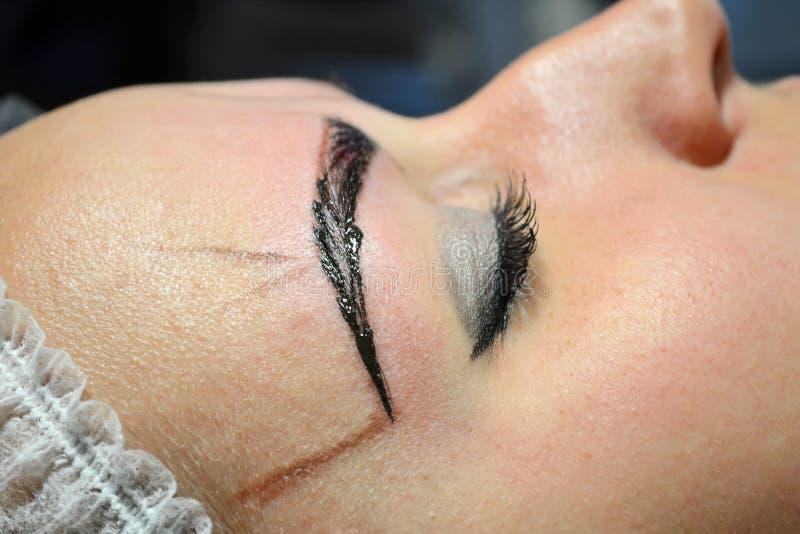 有在在做法的不育的盖帽的构成的女孩microblading与一完成的眼眉 图库摄影