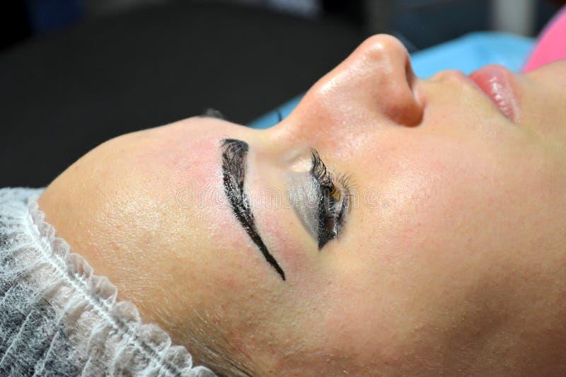 有在在做法的不育的盖帽的构成的女孩microblading与完成的眼眉 免版税图库摄影