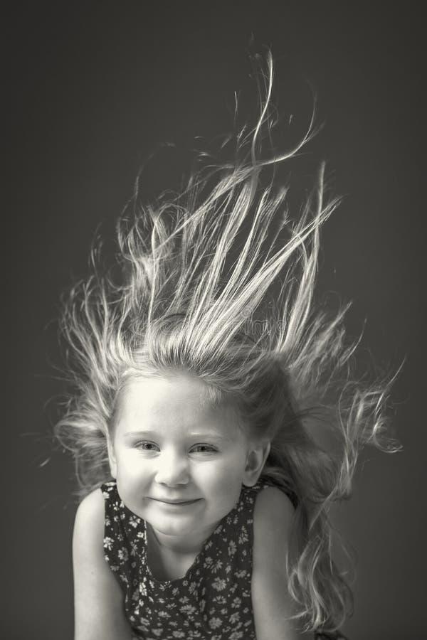 有在天空中举的她的头发的女孩由风 免版税库存照片