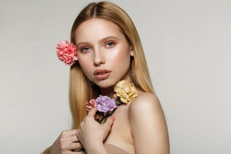 有在头发卷曲的时髦构成和砰花的俏丽的年轻白肤金发的女孩 免版税图库摄影