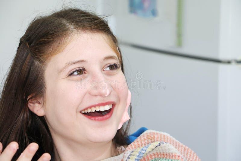 有在她的面孔抹上的甜奶油的一个笑的十几岁的女孩 库存照片