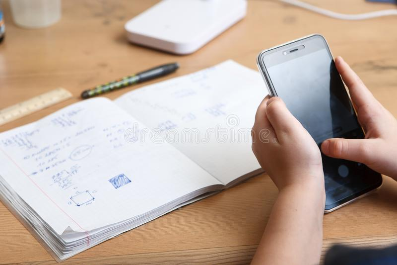 有在家做家庭作业的智能手机的男小学生 免版税库存图片