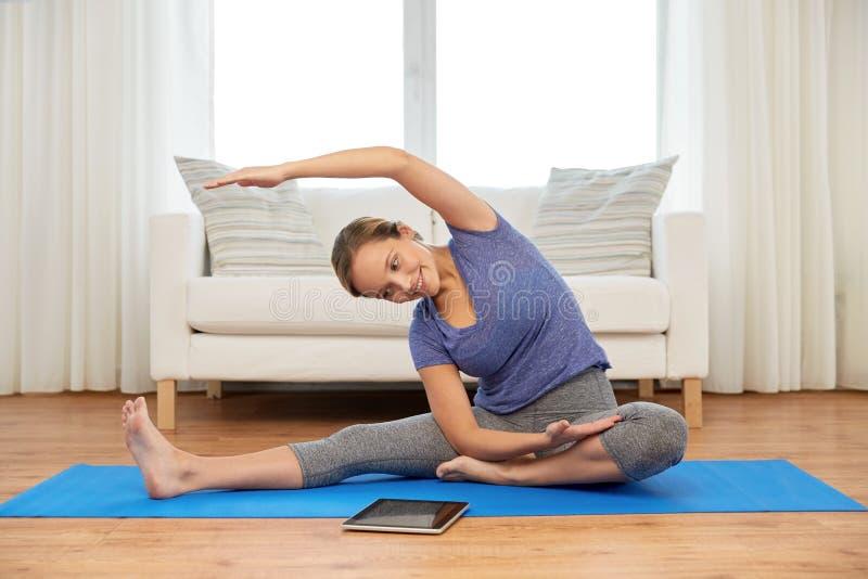 有在家做瑜伽的片剂计算机的妇女 免版税库存照片